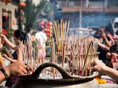 Hands Stab Incense Sticks On Joss Stick Pot Burning And Smoke Used To Pay Respect To Buddha. poster