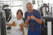 Beautiful Elderly Couple In A Gym. Happy Fitness Couple Holding Dumbbells And Smiling At Camera At F poster