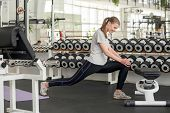 Young Slim Woman Stretching Leg At Gym. Young Sportive Woman Performing Stretching Exercise Before W poster