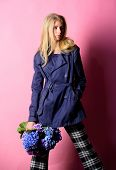 Must Have Concept. Fashionable Coat. Woman Blonde Hair Posing Coat With Flowers Bouquet. Clothes And poster