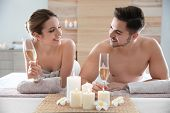 Romantic Young Couple With Champagne In Spa Salon poster