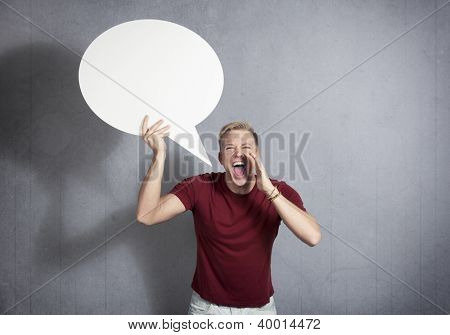 Man shouting loudly while holding white blank speech bubble with space for text isolated on grey background.