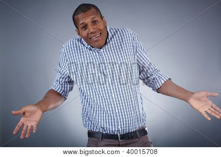 Image of young African man expressing uncertainty over grey background