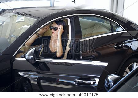 Elegant woman with long legs in car