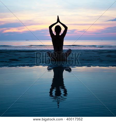 Silhouette of a woman yoga on sea sunset with reflection in water