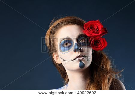 Pretty zombie girl with painted face and two red roses in her hair looks away.