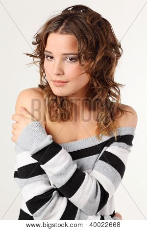 Beautiful girl in striped sweater dreamy smiles and looks away.