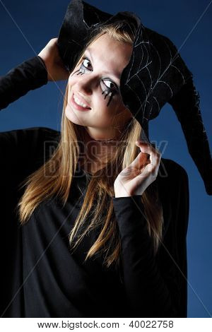 Smiling zombie girl with black tears and cut throat in big black hat.
