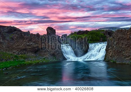 Double waterfall Hjalparfoss on the river Fossa after the midnight sunset with a beautiful vivid dramatic sky and basalt rocks