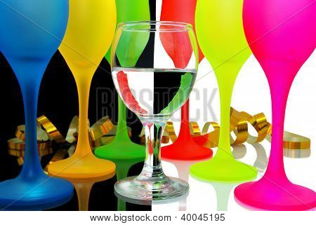transparent glass on a background of colored glasses on black and white glossy background