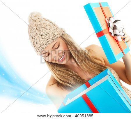 Photo of pretty blond woman in stylish winter hat opening big blue present box, beautiful girl receive Christmas gift, happy young lady holding magic giftbox isolated on white background, New Year eve