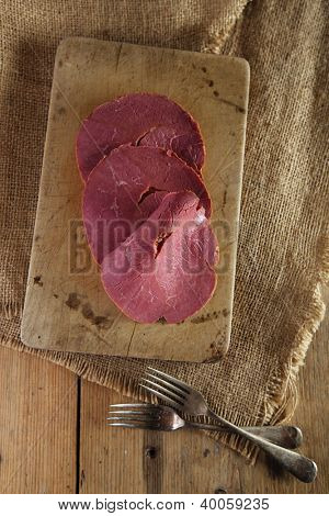 pastrami red meat slices on wooden table with hessian and forks