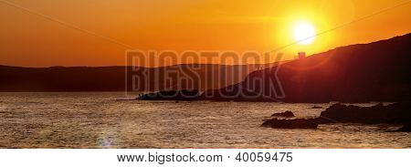 Sunset over ocean panoramic with cliffs and waves.