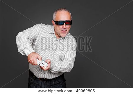senior man in 3d glasses playing in video game and using the joystick over dark background