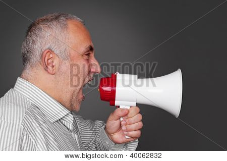 mature man with megaphone over grey background
