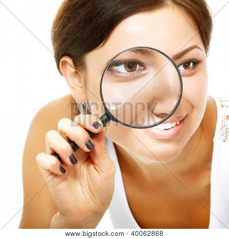 Attractive woman looking through a magnifying glass over white background