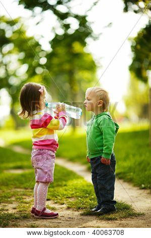 Little Funny Boy And Girl Drinking Mineral Water In Park