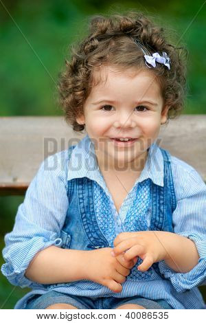 Baby Girl Sitting On A Bench