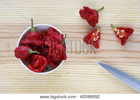 Hot Chilli Peppers In A Bowl Over A Wooden Table.