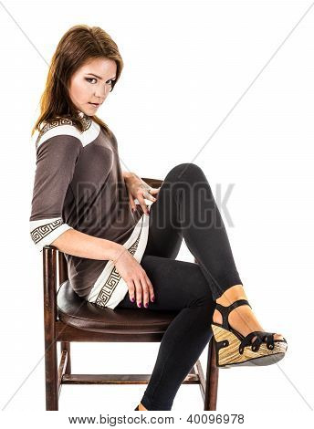The Girl In Sandals Is Sitting On An Old Wooden  .armchair.