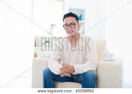 Southeast Asian male sitting on sofa at home