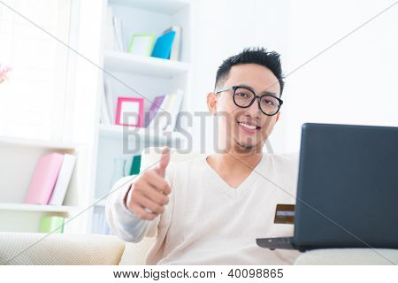 Thumb up Southeast Asian male internet shopping at home