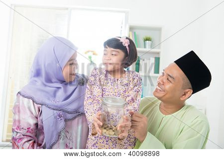 Southeast Asian family. Muslim girl hand holding money jar at home.
