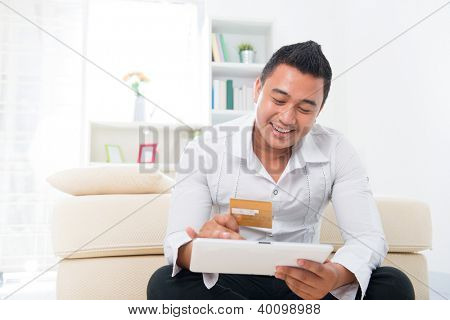 Happy Southeast Asian man online shopping, hands holding credit card and computer tab sitting at home.