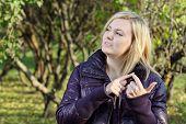 Постер, плакат: Молодая блондинка женщина мечтает и рассчитывает на его пальцы в парке в солнечный осенний день