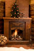 picture of cozy hearth  - Image of hot fire in chimney with fir tree decorated before Christmas - JPG