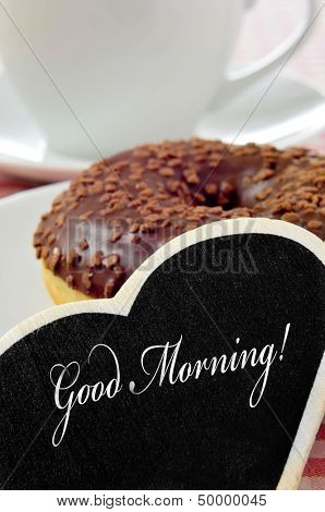 closeup of a heart-shaped blackboard with the sentence good morning written in it and a chocolate coated donut and a cup of coffee or tea in the background