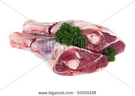 Raw lamb shanks isolated on white, garnished with parsley.