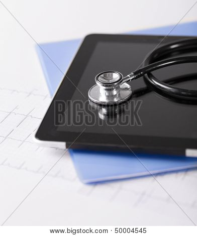 healthcare and technology concept - tablet pc, stethoscope and electrocardiogram
