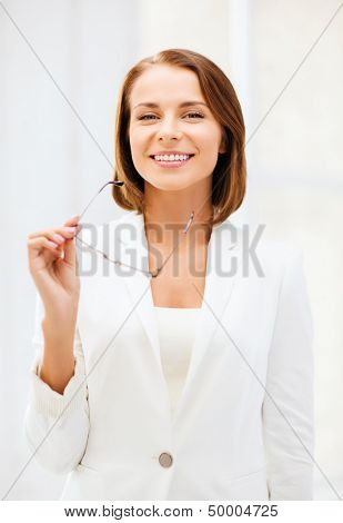 business and vision correction concept - businesswoman with eyeglasses in office