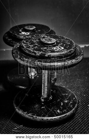 An old but well used set of dumbbells at the gym in black and white.