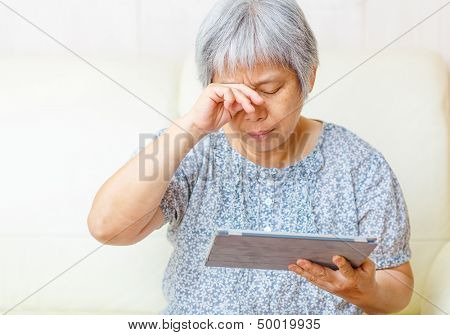 Asian old woman using digital tablet with tired eyes