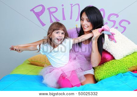 Little girl with mom on bed in room on grey wall background