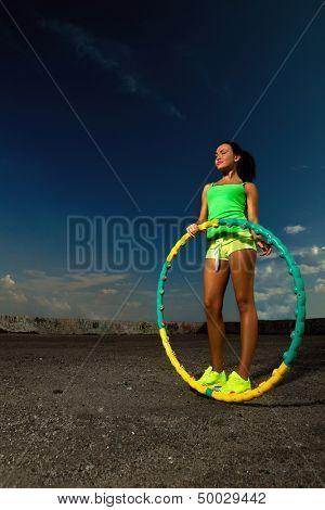 woman rotates hula hoop against blue sky
