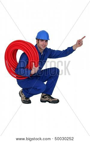 Squatting construction worker pointing his finger