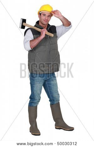 Tradesman carrying a mallet and wearing a hard hat and rubber boots