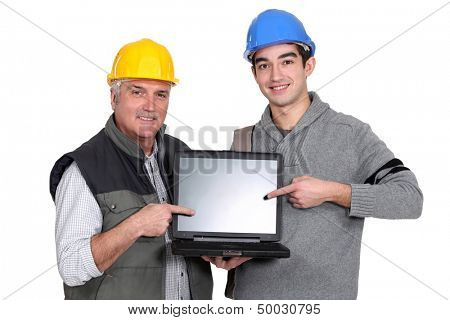 Builder and youth worker pointing at laptop