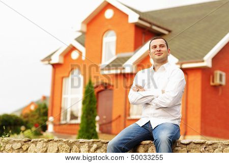 Self-satisfied man in front of his own house.