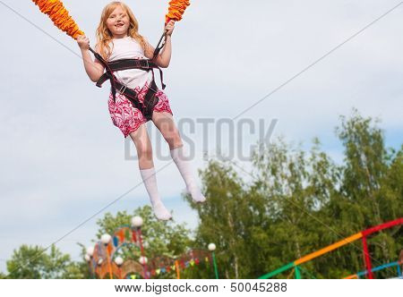 Happy Girl Jumping In Amusement Park
