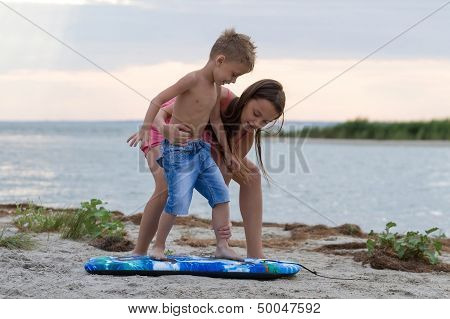 Sister Teaching Her Brother How To Surf