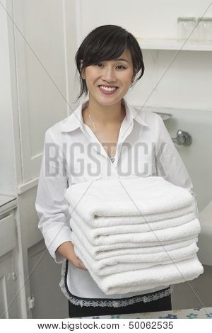 Portrait of young female housekeeper holding clean white folded towels
