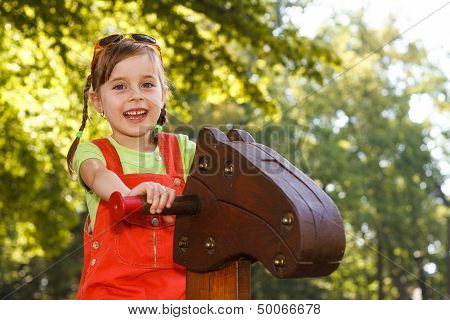 Smiling Girl Riding Wooden Horse On The Playground