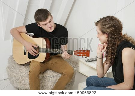 Young man strumming guitar besides female friend