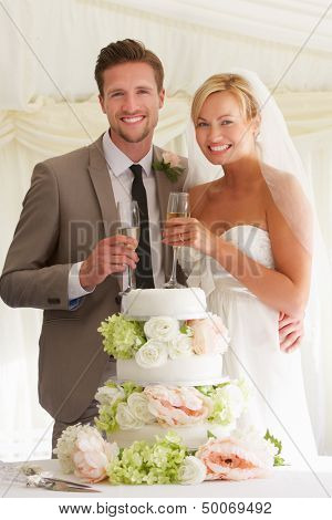 Bride And Groom With Cake Drinking Champagne At Reception