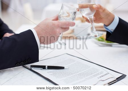 Close up of business partners clinking glasses after a concluded deal