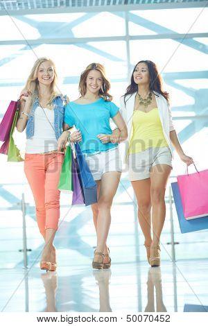 Retrato de três namoradas glamorosos com paperbags andando do centro de comércio
